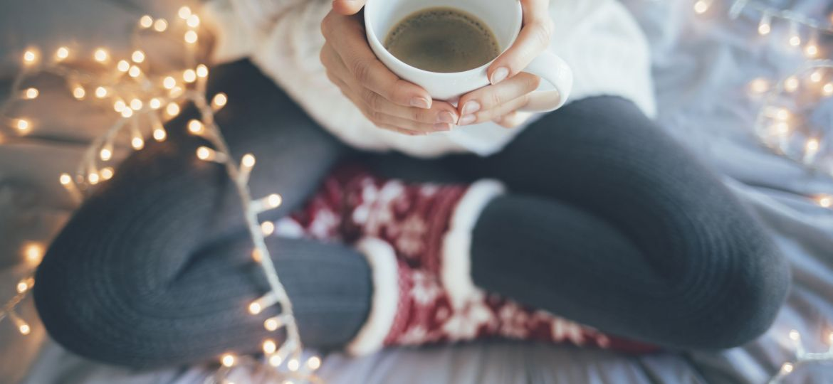 Woman sitting legs crossed on bed and holding a cup